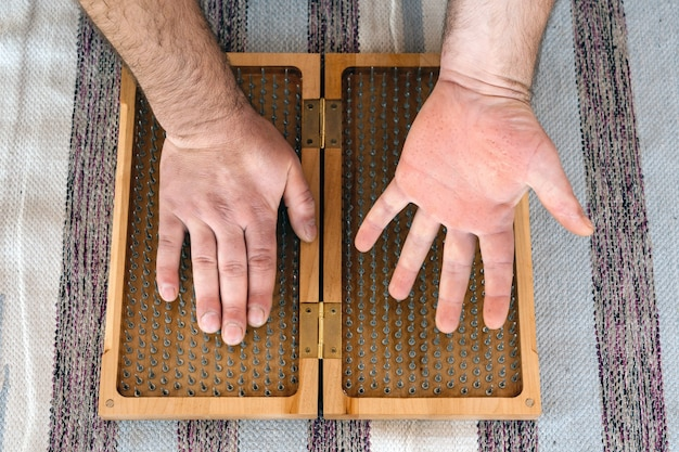 Mann, der yoga-holz-sadhu-brett mit scharfen nägeln berührt