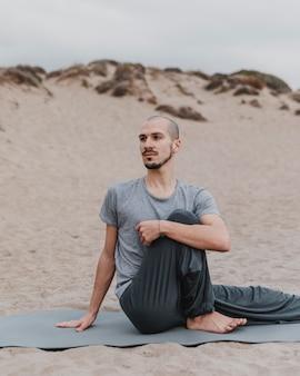Mann, der yoga im freien ausübt