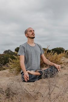 Mann, der yoga im freien praktiziert
