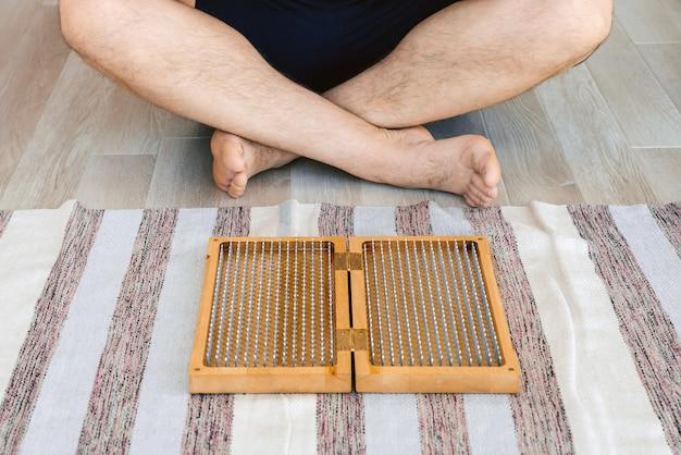 Mann, der yoga meditiert, das sitzende hände meditiert, verbunden auf dem boden nahe einem sadhu brett