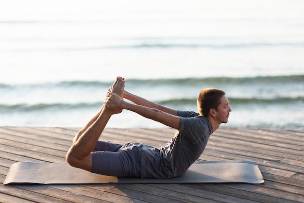 Mann, der yoga nahe meer tut
