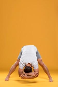 Mann, der yogaübung tut