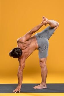 Mann, der yogaübungen tut