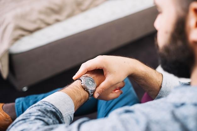 Mann, der zeit auf armbanduhr überprüft