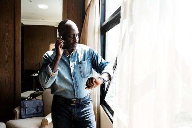 Mann, der zeit von der uhr im hotelzimmer überprüft
