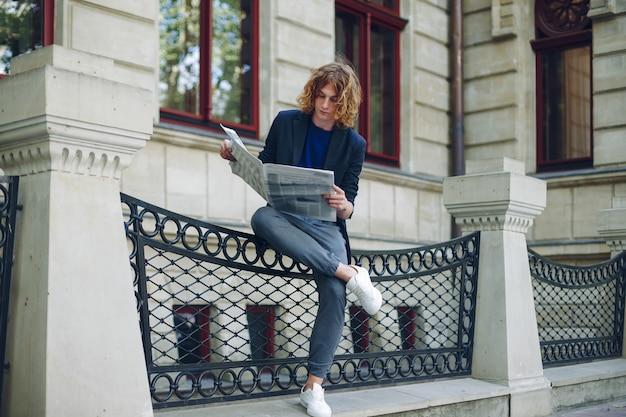 Mann, der zeitung nahe altem stilgebäude liest