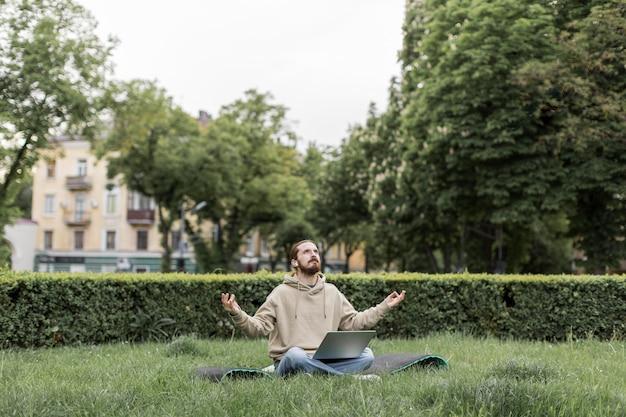 Mann, der zen im stadtpark mit laptop fühlt