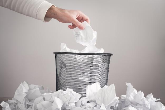 Mann, der zerknittertes papier in mülleimer wirft.