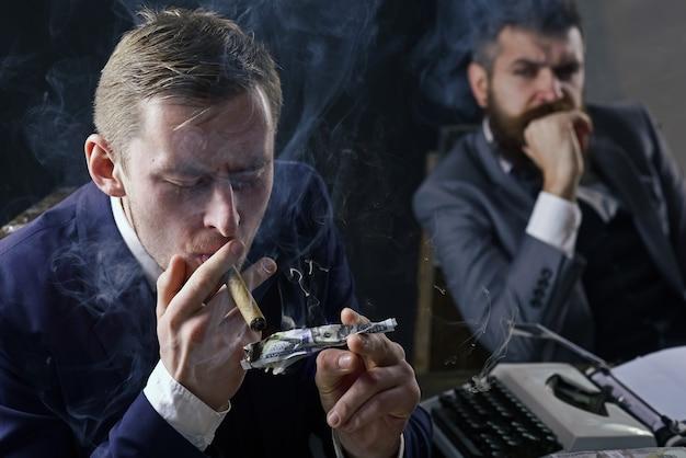 Mann, der zigarre aus brennenden banknoten anzündet geschäftsmann raucht zigarre bei geschäftstreffen verschwenden konzept geschäftsleute in anzügen sitzen am tisch mit schreibmaschine und geld im dunklen innenraum defokussiert