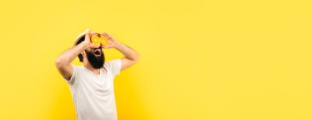 Mann, der zitronenscheiben vor augen, über gelbem hintergrund hält