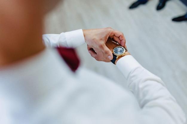 Mann, der zu der zeit auf seiner armbanduhr schaut
