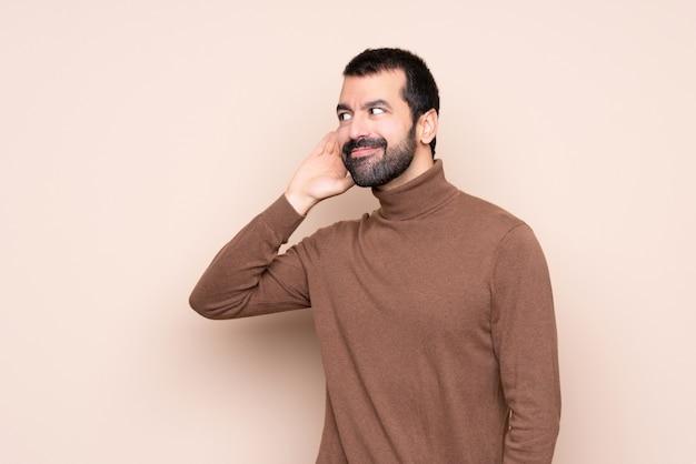 Mann, der zu etwas hört, indem er hand auf das ohr setzt
