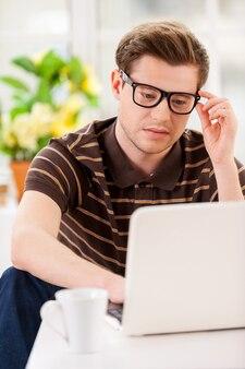 Mann, der zu hause arbeitet. selbstbewusster junger mann, der am laptop arbeitet und seine brille justiert, während er in seiner wohnung auf dem boden sitzt