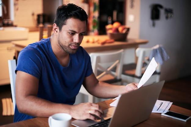 Mann, der zu hause einen laptop benutzt
