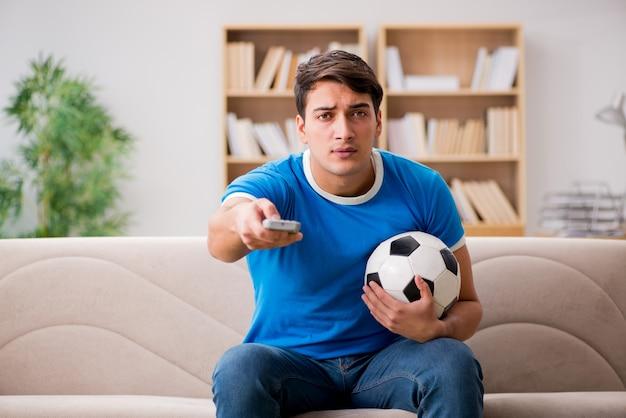 Mann, der zu hause fußball aufpasst