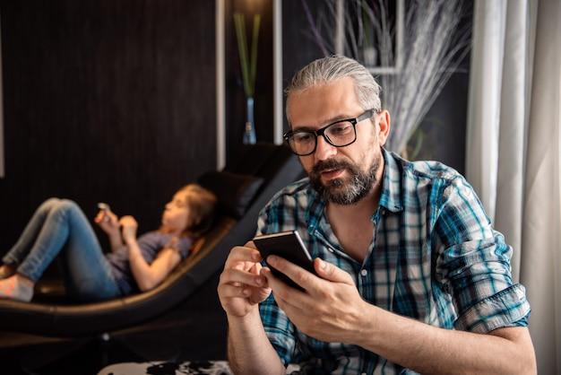 Mann, der zu hause intelligentes telefon verwendet