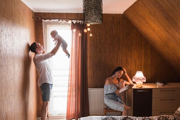 Mann, der zu hause mit seinem baby während frauenlesebuch spielt