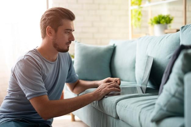 Mann, der zu hause seinen laptop mit digitalem assistenten benutzt