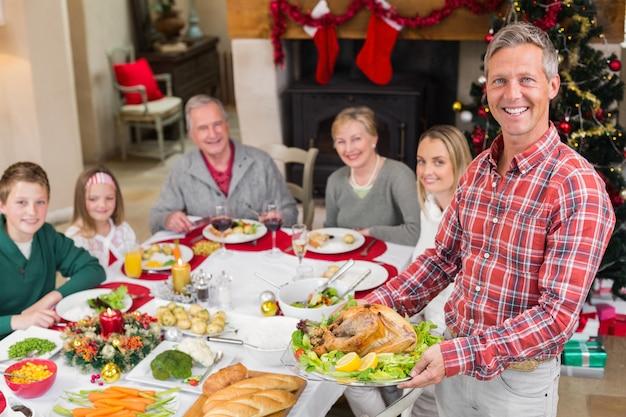 Mann, der zu hause truthahnbraten mit familie am speisetische im wohnzimmer hält