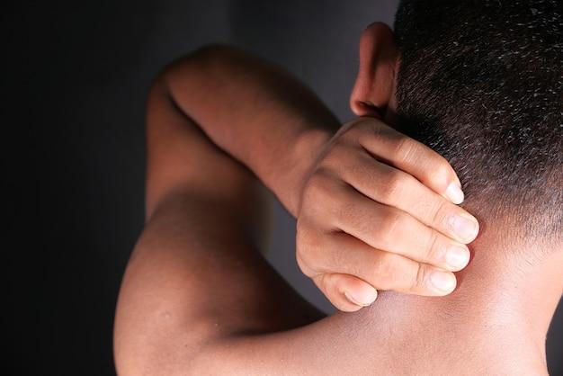 Mann, der zu hause unter nacken- oder schulterschmerzen leidet.