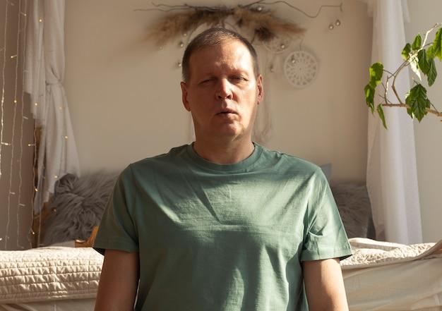 Mann, der zu hause yoga und atemkontrolle praktiziert und in gemütlichem schlafzimmer im öko-stil meditiert.