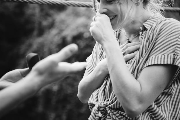 Mann, der zu seiner glücklichen freundin mit ring vorschlägt