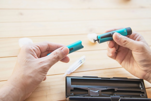 Mann, der zuckerkranke spritze des insulins für einspritzung vorbereitet