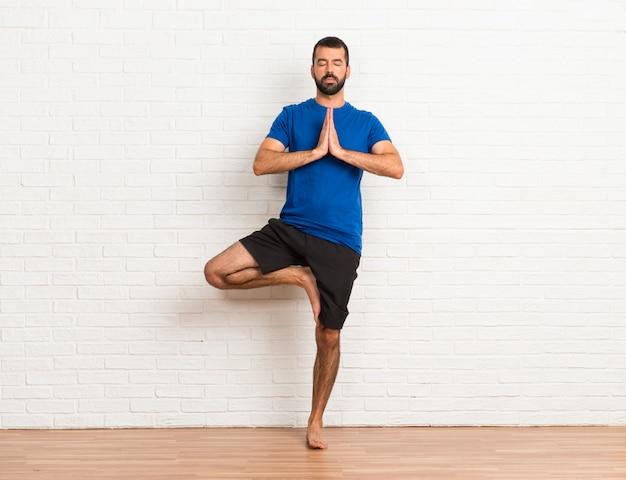 Mann, der zuhause yogaübungen tut
