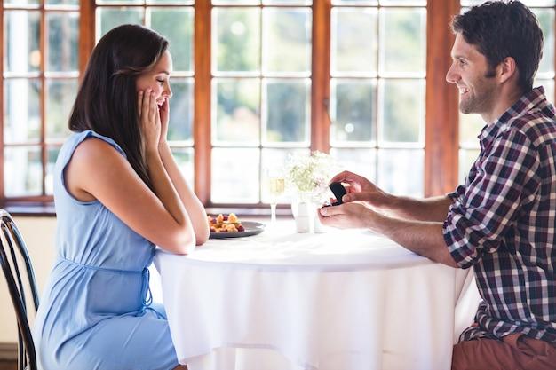 Mann, der zur frau in einem restaurant vorschlägt