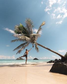 Mann, der zur gebogenen palme in der küste springt