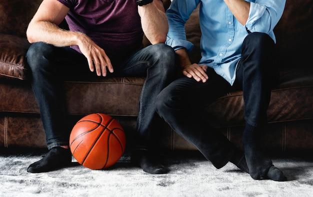 Mann, der zusammen auf einem aufpassenden sport der couch sitzt