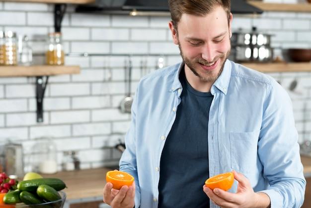 Mann, der zwei orange scheiben in der küche betrachtet