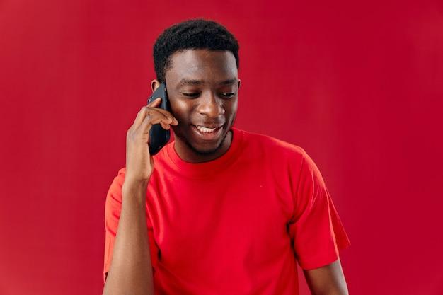 Mann des afrikanischen aussehens, der am telefon rot spricht