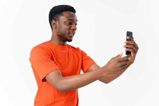 Mann des afrikanischen aussehens in einem orangefarbenen t-shirt auf einem lichthintergrund beschnittenen ansichtsmodellkopierraum