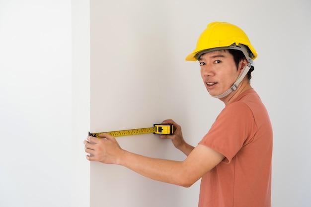 Mann des asiatischen inneningenieurs mit gelbem helm, der maßband verwendet, um leere wand des neuen hauses zu messen. eingebaute möbel oder schränke für ein modernes, leeres zuhause. immobilienbranche.