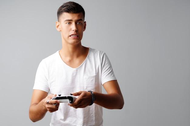 Mann des jungen jugendlich, der mit konsolensteuerknüppel über einem grauen hintergrund spielt