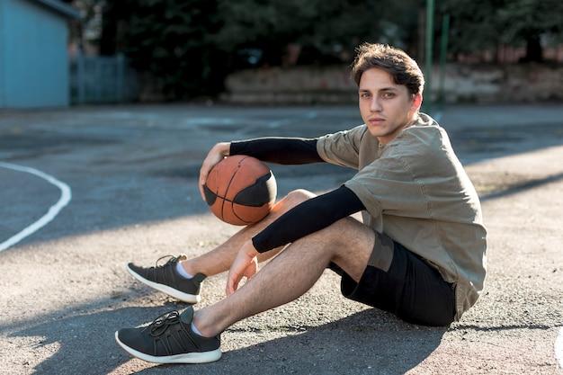 Mann des jungen mannes, der auf basketballplatz sitzt