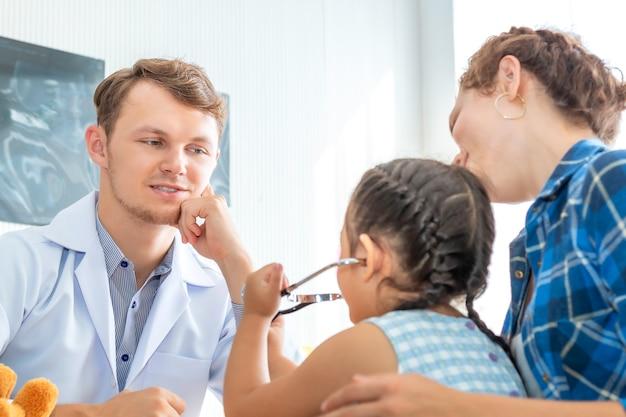 Mann des kinderarztes (doktor), der patienten des kleinen mädchens unter verwendung eines stethoskops im krankenhaus überprüft.