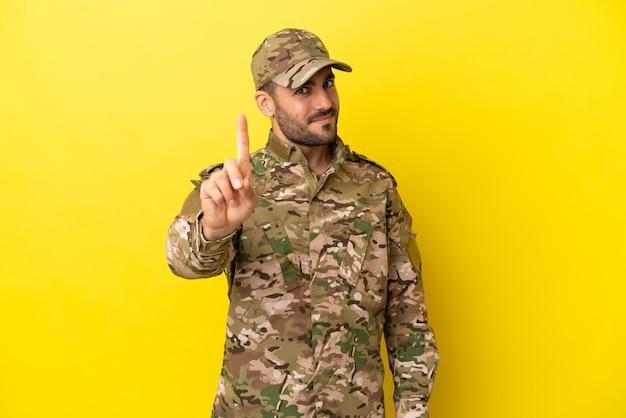 Mann des militärs isoliert auf gelbem hintergrund, der einen finger zeigt und hebt