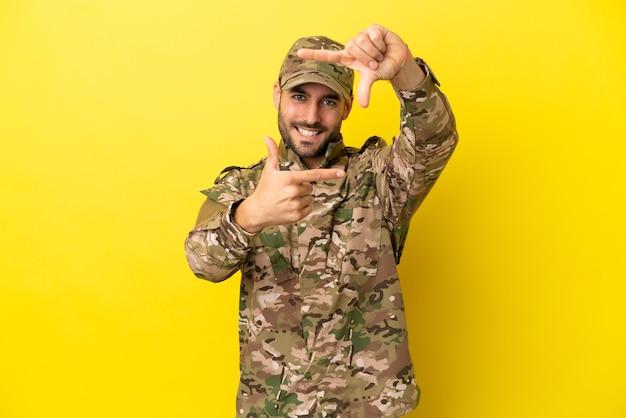 Mann des militärs lokalisiert auf dem fokusgesicht des gelben hintergrundes. rahmensymbol