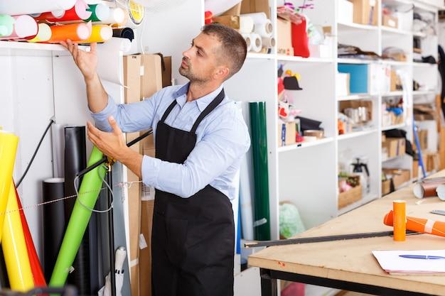 Mann-designer und druck-operator mit vinyl-papier bei der druckherstellung