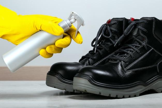 Mann desinfiziert schuhe. desinfizieren von stiefeln vor dem betreten eines arbeitsplatzes.