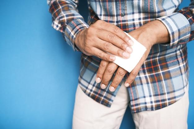 Mann desinfiziert seine hände mit einem feuchten tuch
