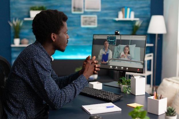 Mann diskutiert mit ferntherapeut über krankheitssymptome der tochter während der videoanruf-telemedizin-konferenz... arzt erklärt die behandlung im gesundheitswesen. online-telearbeitsberatung