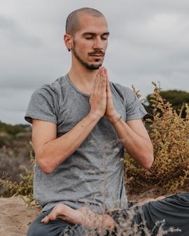 Mann draußen yoga machen