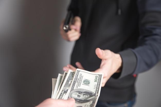 Mann droht mit einer waffe und nimmt geld von einem geschäftsmann