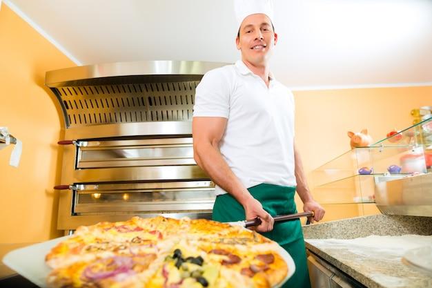 Mann drückt die fertige pizza aus dem ofen