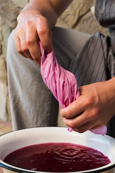 Mann drückt stoff aus rosa natürlichem pigment