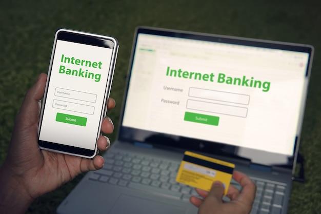 Mann durchsuchte die homepage des internet-banking-dienstes auf seinem smartphone und laptop mit kreditkarte. mobile-banking-konzept für online-zahlungen. geschriebene wörter internet-banking auf telefon- und notebook-bildschirmen.