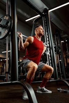 Mann ein athlet ist in einem fitnessstudio beschäftigt und macht eine übung an den muskeln der arme bizeps schwarzer hintergrund. hochwertiges foto.